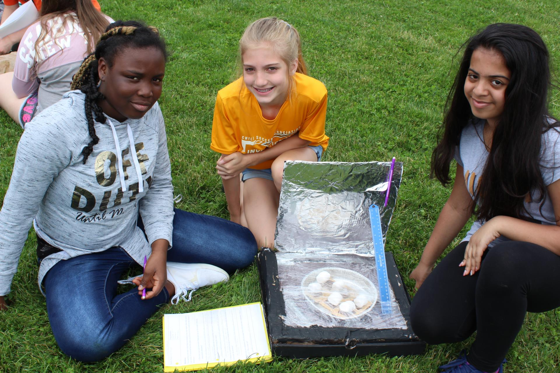 Three students with their solar cooker