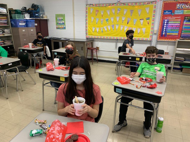 Students enjoying hot cocoa at their desks