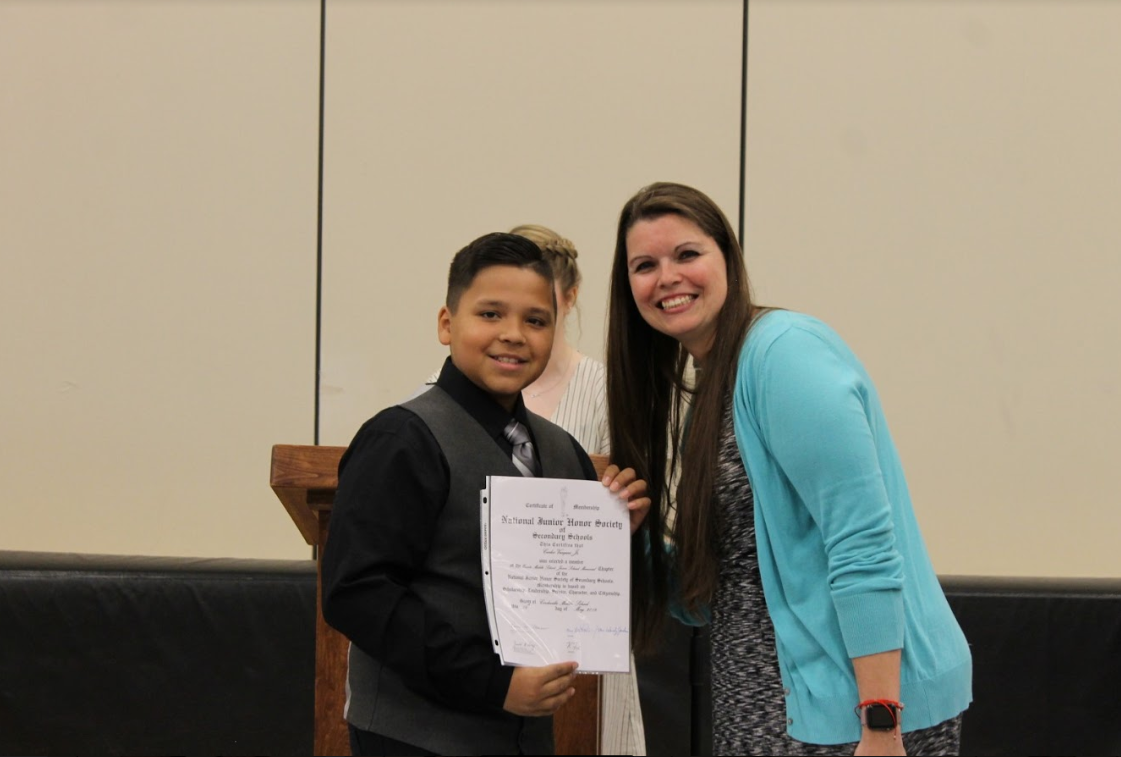 National Junior Honor Society inductee Carlos Vazquez receives his certificate from chapter advisor Mrs. Lisa Powers.