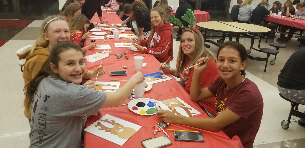 Students eat at a canvas and pizza party.