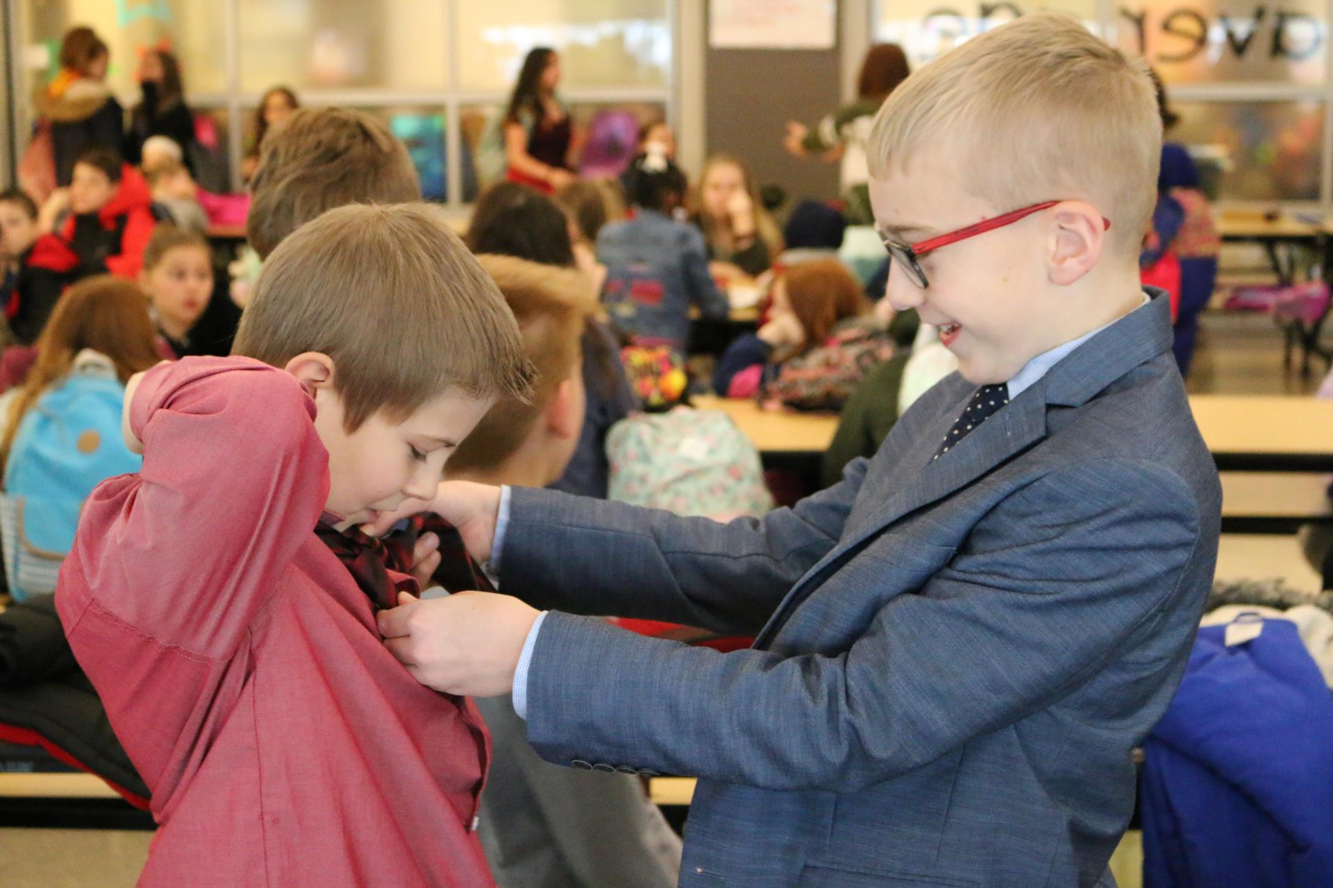 Student helps another student tie a tie.