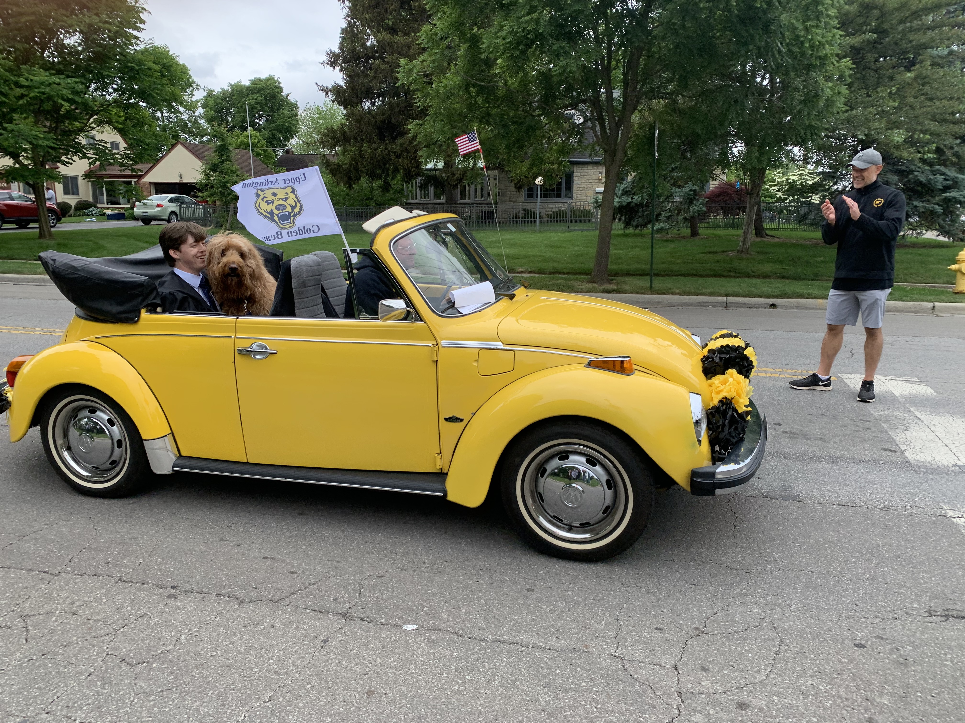 A graduate with his dog in the car parade